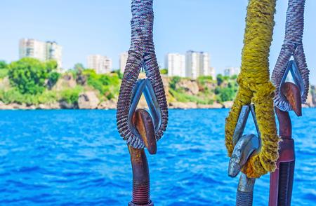 city park boat house: The rusty hooks and dusty ropes of the tourist yacht, sailing along the coast of Antalya, Turkey.
