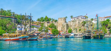ANTALYA, TURKEY - MAY 12, 2017: The replicas of medieval pirate galleons look authentic in preserved medieval port of resort with remains of tall fortress ramparts and historic edifices, on May 12 in Antalya.