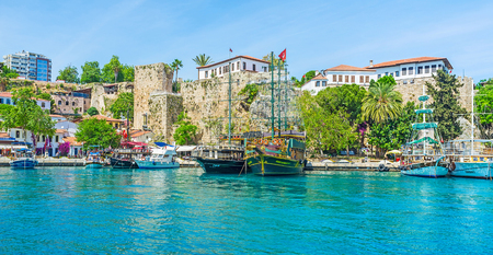 ANTALYA, TURKEY - MAY 12, 2017: The picturesque old marina with stone ramparts, popular fish taverns, souvenir stores and tourist boats, on May 12 in Antalya.