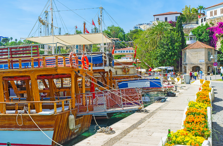 ANTALYA, TURKEY - MAY 12, 2017: The walk along the tourist boats in old marina with a view on historic Iskele Mosque, located at the foot of the cliff and fortress wall, on May 12 in Antalya.