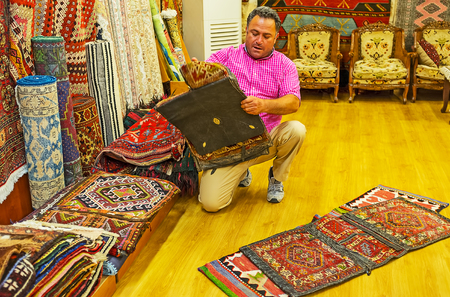 ANTALYA, TURKEY - MAY 12, 2017: The vendor of carpet store demonstrates the antique hand knotted camel saddle bags, Old Bazaar, on May 12 in Antalya.