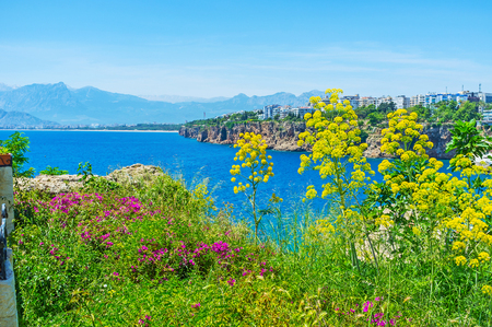 city park boat house: The beautiful seascape of Antalya from the tall cliff, covered with lush greenery and flowers, Mermerli park, Turkey. Stock Photo