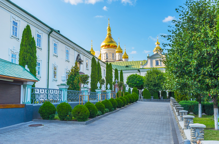 The courtyard of brotherhoods corps with narrow alley surrounded with monastery garden, Pochaev, Ukraine Stock Photo