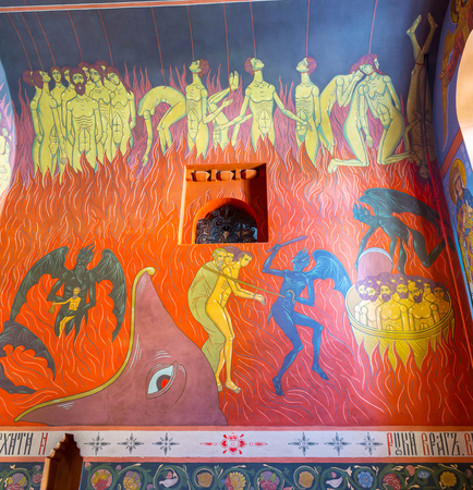 POCHAYIV, UKRAINE - AUGUST 30, 2017: Colorful frescoes representing hell, painted on the Wall of Holy Trinity Cathedral, on August 30 in Pochayiv. Editorial