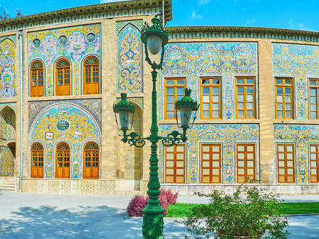 The green vintage streetlight in front of the richly decorated wall of Golestan palace, Tehran, Iran. Stock Photo