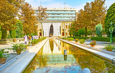 TEHRAN, IRAN - OCTOBER 11, 2017: Enjoy the colors of fall and medieval Persian architecture in Golestan Palace complex with ponds, fountains, lush trees and splendid edifices, on October 11 in Tehran.