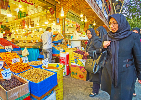 TEHRAN, IRAN - OCTOBER 11, 2017: The  crowded Panzdah-e-Khordad street is famous place among locals and tourists, visiting Grand Bazaar and choosing interesting and tasty goods in traditional stalls, on October 11 in Tehran.