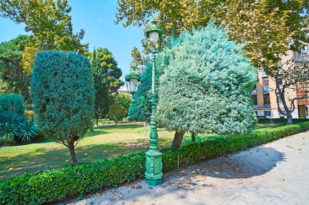 The walk in shade of Golestan garden with trimmed bushes, coniferous trees and palms and the old fashioned streetlights, Tehran, Iran.