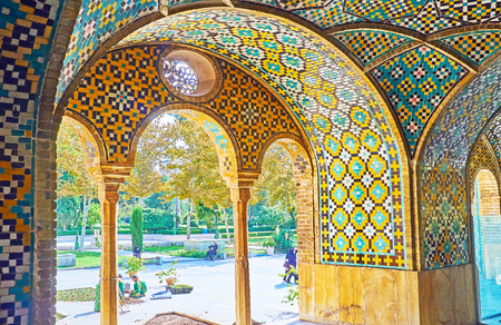 TEHRAN, IRAN - OCTOBER 11, 2017: The shady green garden of Golestan palace is seen through the arches of Karim Khani Nook, the idyllic pavilion, where Persian Shahs liked to relax, on October 11 in Tehran.