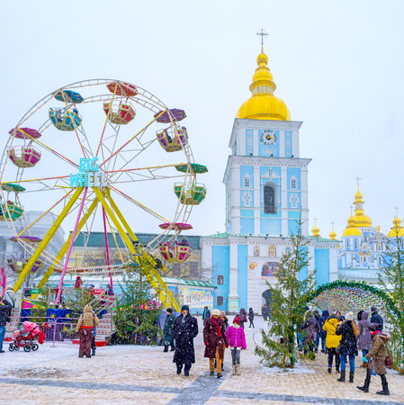 KIEV, UKRAINE - JANUARY 4, 2017:  The St Michael Square is full of people, enjoying the Christmas festivity, visiting carousels with kids and making pictures of local landmarks, on January 4 in Kiev. Editorial