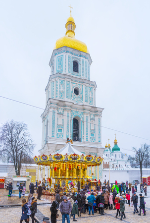 KIEV, UKRAINE - JANUARY 4, 2017:  St Sophia Square is the main destination of Christmas festivity, here locates Christmas Tree, Market stalls, carousels and attractions for kids, on January 4 in Kiev. Editorial