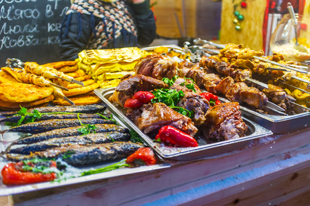 Hot prepared grilled meat and fish on the counter of food stall at Christmas Fair in Kiev, Ukraine