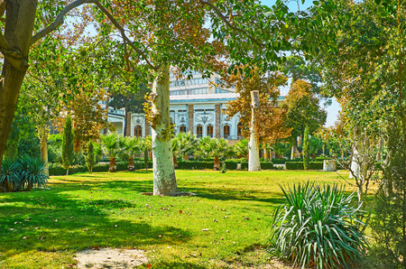 The walk among the palms and sycamore trees of Golestan garden with a view on white wall of Abyaz palace through the branches, Tehran, Iran. Editorial