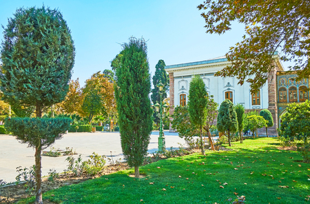 The ornamental Golestan garden with trimmed coniferous trees, juicy green lawn and wide alleys between the edifices, Tehran, Iran.