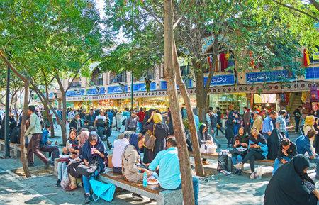 テヘラン, イラン-10 月 11, 2017: テヘランで10月11日に、人々は混雑した Panzdah のベンチに座って、バックグラウンドで複数のグランドバザールの屋台を Khordad して、ランチを楽しんでいます。 写真素材 - 89571105