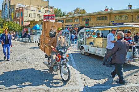 TEHRAN, IRAN - OCTOBER 11, 2017: The  Panzdah-e-Khordad street with chaotic traffic, crowded roadside, open air tourist bus and a bike, delivering big boxes to some store of Grand bazaar, on October 11 in Tehran.