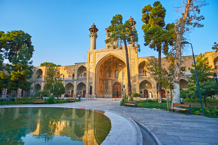 The walk in scenic garden of Sepahsalar (Shahid Motahari) mosque with shady alley, scenic pond and many benches to rest in peaceful place, Tehran, Iran.