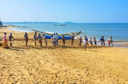 BENTOTA, SRI LANKA - DECEMBER 6, 2016: The fishermens crew pull the net, standing in line on the sand coast, on December 6 in Bentota. Editorial