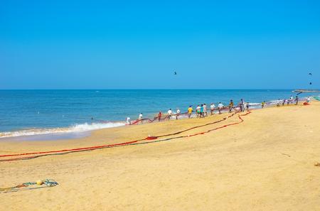 The hard work of Sri Lankan fishermen, pulling heavy nets from the ocean, Bentota.