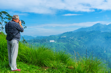 The tourist makes photos of the scenic mountain landscapes and Ella Gap from the Little Adams Peak, Sri Lanka.
