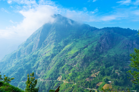 The picturesque Ella Rock  with emerald green slopes is partly hidden in white morning clouds, Sri Lanka.
