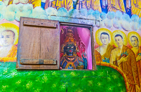KETAWALA, SRI LANKA - DECEMBER 1, 2016: The blue statue of Lord Buddha in niche of Bogoda Temple, surrounded with paintings of bhikkhu monks, on December 1 in Ketawala.
