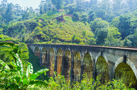 The beautiful Nine Arch Bridge among the lush greenery of Sri Lankan highlands with the huge mountain slope on the background, Damodara, Ella.