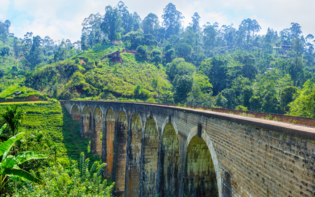 The gardens and forests on mountains of Demodara surround the Nine Arch Bridge - the great stone construction and main landmark of highland resort, Ella, Sri Lanka.