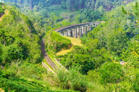 Nine Arch Bridge is one of main attractions of resort, people come to watch the trains, running through the lush jungle along the great stone construction, Demodara, Ella, Sri Lanka. Stock Photo