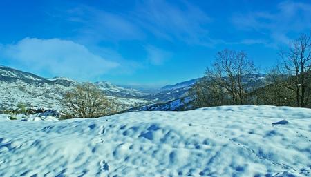 Die Vogelspuren im Schnee auf dem Hügel mit den Pindus-Bergen auf dem Hintergrund, Griechenland.