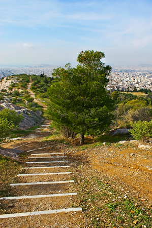 The walk along the hilltop of the Muse (Nymphs, Philopappos) Hill, the footpath leads to the viewpoint, overlooking the cityscape of Piraeus, Athens, Greece. Stock Photo