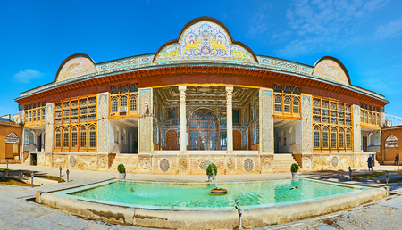 SHIRAZ, IRAN - OCTOBER 12, 2017: Panorama of Qavam House with mirror terrace in the middle, decorations of tiled patterns, carved wood, stained glass windows and scenic fountain, on October 12 in Shiraz.