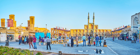 YAZD, IRAN - OCTOBER 17, 2017:  Panoramic view on Amir Chakhmaq square with locals and tourists, taking pictures with a view on beautiful ensemble of the square, on October 17 in Yazd