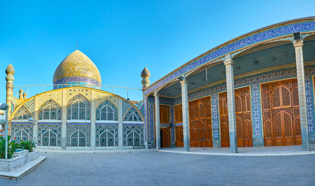 Panoramic view on beautiful Hazayer mosque with big stained glass windows and side portal with carved shutters on its windows, Yazd, Iran