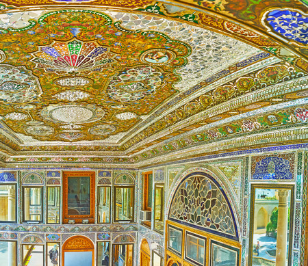 SHIRAZ, IRAN - OCTOBER 12, 2017: The wooden ceiling of mirror veranda in Qavam (Ghavam) House of Naranjestan is covered with colored painted patterns and complex decors of mirror pieces, on October 12 in Shiraz. Editorial