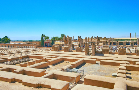 The building of Persepolis Treasury located behind the buildings foundations and is neighboring with ruined palaces of the complex, Iran.