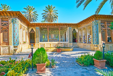 SHIRAZ, IRAN - OCTOBER 12, 2017: The  shady courtyard of Zinat Ol-Molk complex is occupied with perfect garden, surrounded by preserved medieval buildings, on October 12 in Shiraz. Editorial
