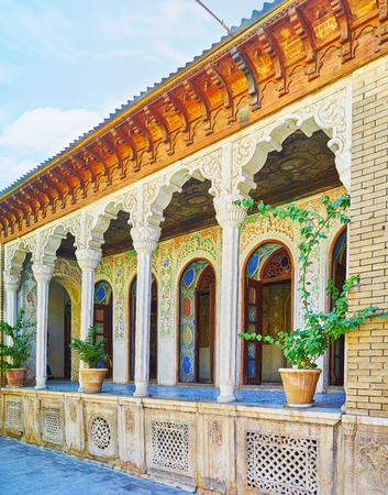 SHIRAZ, IRAN - OCTOBER 12, 2017: The  scenic arched galley of Zinat Ol-Molk mansion with rich patterns of carved plaster, slender pillars and fine paintings on ceiling, on October 12 in Shiraz. Editorial