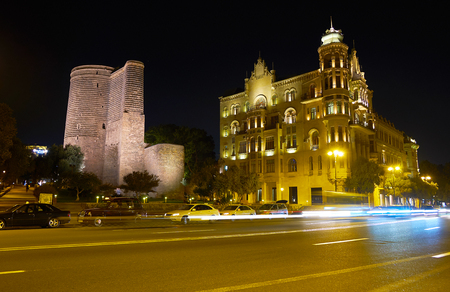 BAKU, AZERBAIJAN - OCTOBER 9, 2017: Beautiful medieval Maiden Tower neighbors with modern De Gaulle house on Neftchilar Avenue, on October 9 in Baku Editorial