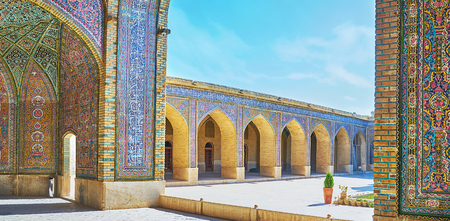The arched gallery of Nasir Ol-Molk mosque is covered with complex tiled decorations and calligraphy from Quran, Shiraz, Iran. 스톡 콘텐츠