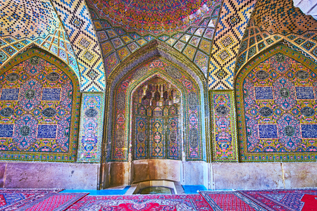 SHIRAZ, IRAN - OCTOBER 12, 2017: The tiled mihrab in Nasir Ol-Molk mosque with fine patterns and muqarnas details, on October 12 in Shiraz.
