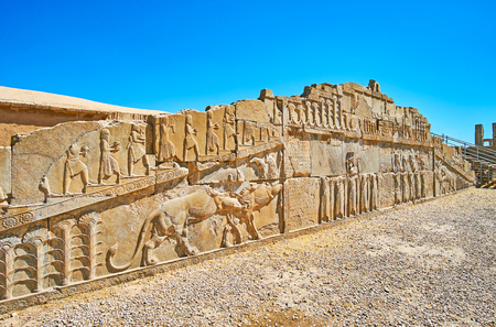 The ruined facade wall of the ancient palace of Xerxes (Hadish) with preserved reliefs, including classical Persian themes - lion and bull, soldiers and courtiers with tributes, Persepolis, Iran.
