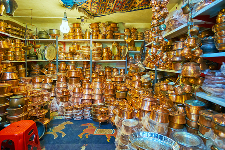 SHIRAZ, IRAN - OCTOBER 12, 2017: The Ordu Bazaar is famous for its numerous copper workshops and cookware stalls, offering wide range of copper pans, pots, cups and trays, on October 12 in Shiraz. Editorial