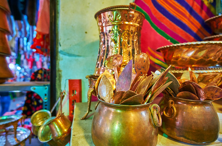Different shaped handmade copper spoons in pot, Ordu Bazaar of Shiraz, Iran.
