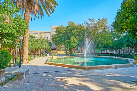 The scenicshady garden of Madraseh-ye Khan with the fountain in the middle, stone banches and pieceful atmosphere, Shiraz, Iran. Stock Photo