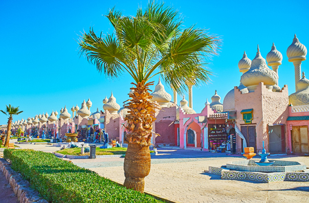 The walk in park with green palms with a view on modern pavilions of Alf leila wa leila (1001 nights) bazaar, Sharm El Sheikh, Egypt.