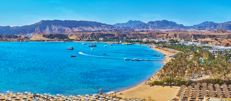 Sharm El Maya is one of the central districts of resort, that boasts scenic rocky landscape and beautiful beaches with palms and multiple sunshades, Sharm El Sheikh, Egypt. Stock Photo