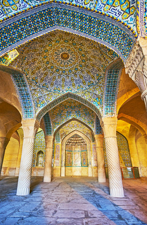 SHIRAZ, IRAN - OCTOBER 12, 2017: The shabestan (prayer hall) of Vakil Mosque with beautiful tiled vault, stone columns and muqarnas details in mihrab, on October 12 in Shiraz.