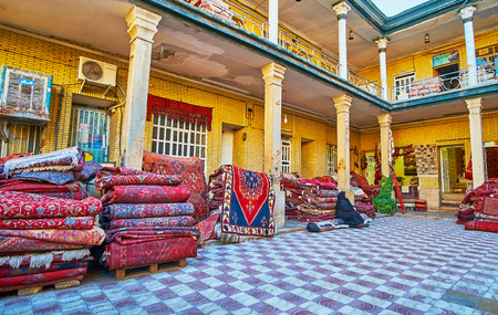 SHIRAZ, IRAN - OCTOBER 12, 2017: The heap of Persian carpets in yard of warehouse-store, located next to central carpet market, on October 12 in Shiraz, Iran. Editorial