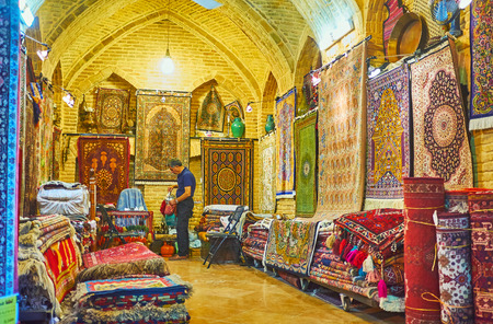 SHIRAZ, IRAN - OCTOBER 12, 2017: Interior of traditional carpet store in Vakil Bazaar, the carpets and rugs lie on the floor and hang on the walls, on October 12 in Shiraz.